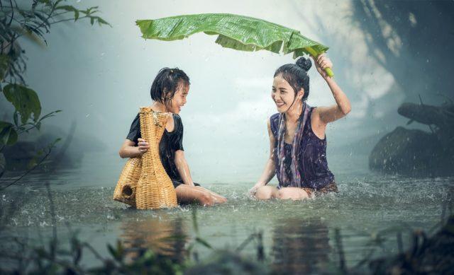 葉っぱで雨をしのぐ女